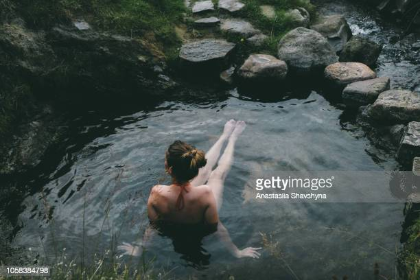 woman resting in wild hot spring in iceland - hot spring stock pictures, royalty-free photos & images