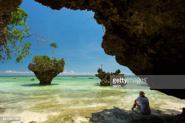 woman resting on a wild beach in zanzibar, tanzania. - zanzibar island stock photos and pictures
