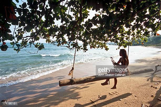 Woman resting on beach swing.