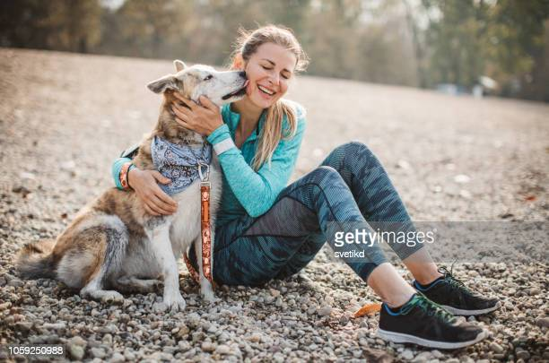 woman resting on beach with dog - dog stock pictures, royalty-free photos & images