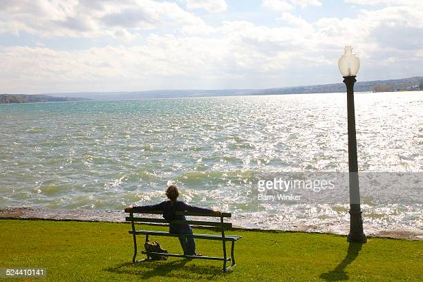 woman resting on bench, finger lakes - skaneateles lake stock pictures, royalty-free photos & images