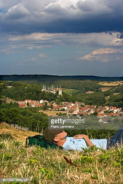 Woman resting on grass, focus on village and Castle of La Rochepot in background, side view