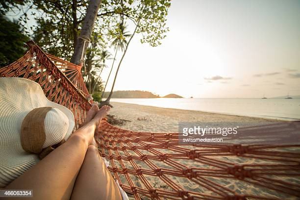 woman resting on hammock on tropical beach - escapism stock photos and pictures