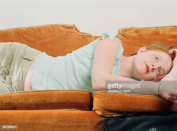 woman resting on sofa - jessamyn harris stock pictures, royalty-free photos & images