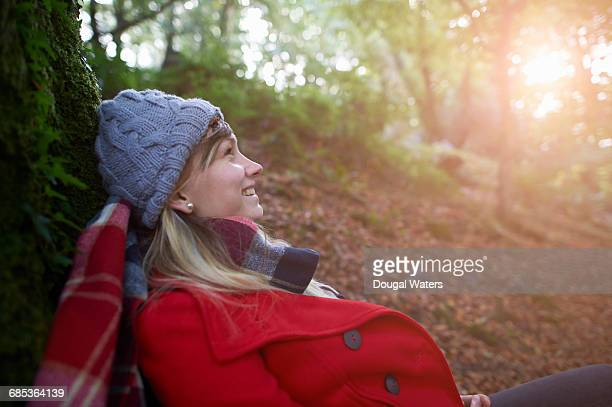Woman resting on tree trunk in forest.