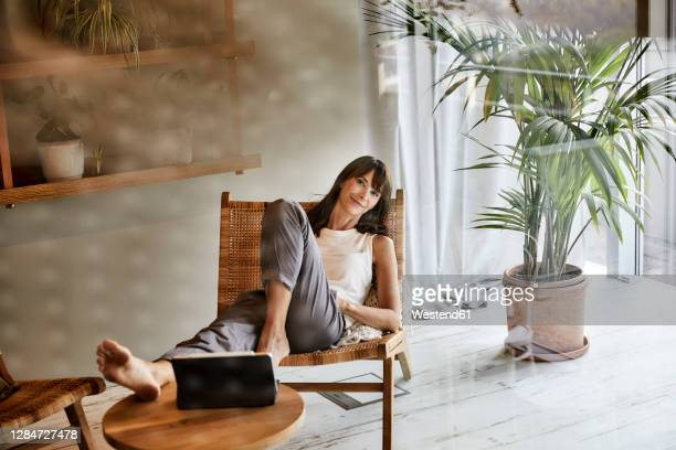 woman resting while sitting on chair at home - resting fotografías e imágenes de stock