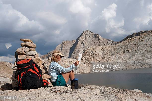 Woman rests and references map in mountains
