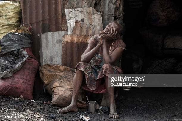 A woman rests in the Mindara neighbourhood in Bissau on Mardi Gras on February 13 2018 / AFP PHOTO / Xaume Olleros