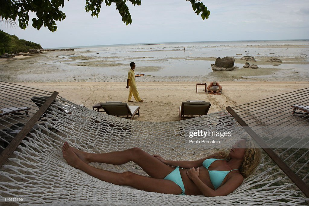 A woman rests on a hammock at the beach at the Kamalaya Wellness Sanctuary June 18, 2012 . Thailand's official tourism body, the Tourism Authority of Thailand (TAT) has set itself the ambitious target of attracting more than 20 million tourists in 2012. According to TAT, In April, Thailand welcomed 1,659,021 international tourists which is a slight increase of 6.87% over the same in 2011.