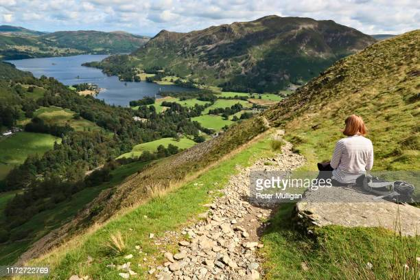 a woman rests on a rock overlooking ullswater and patterdale - english lake district - lake district stockfoto's en -beelden