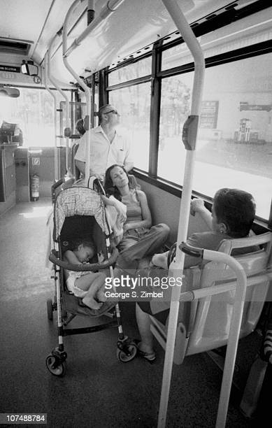 A woman rests on a seat in a bus while her son sleeps in a stroller next to her Valencia Spain April 2010