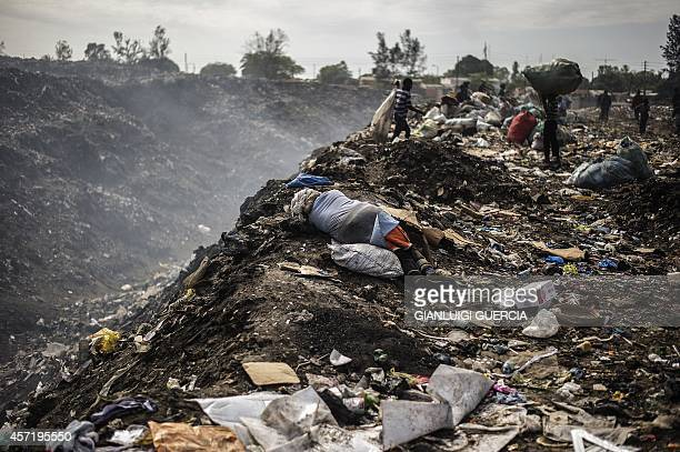 A woman rests on the ground as rubbish pickers sift through garbage at the Maputo municipal garbage dumping site in Maputo on October 14 2014...