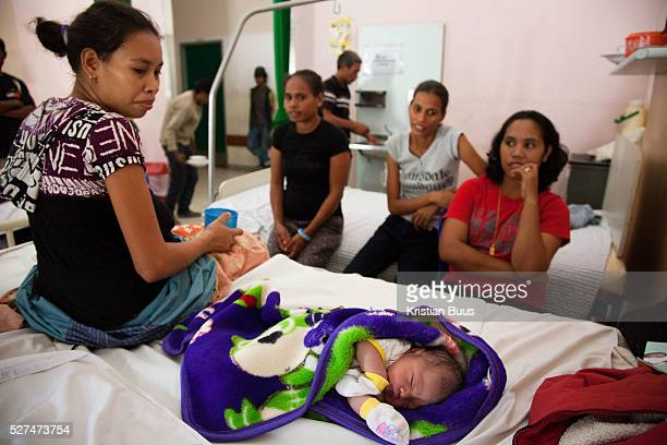 A woman rests on the maternity ward next to her new born baby Infant mortality rates are very high in TimorLeste and one of the reasons for that is...