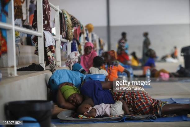 Woman rests with her baby on the ground at the Pemba Sports center that is now a shelter in Pemba on April 2, 2021. - People were evacuated from the...