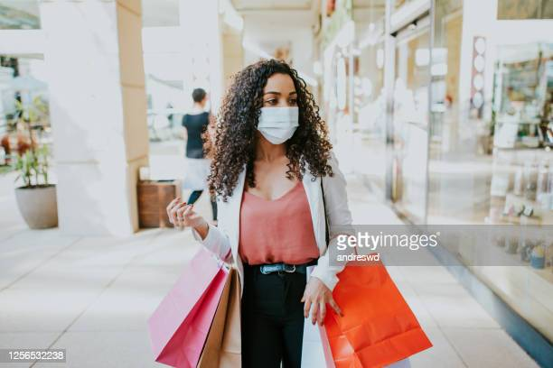 a woman returning to shopping at the mall with a face mask - opening event stock pictures, royalty-free photos & images