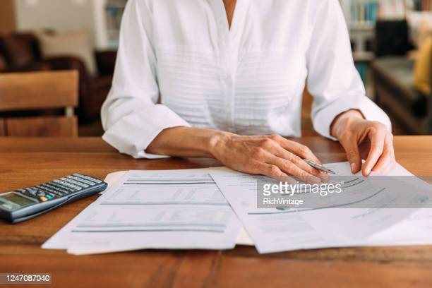 woman reviewing financial figures - northern european descent stock pictures, royalty-free photos & images