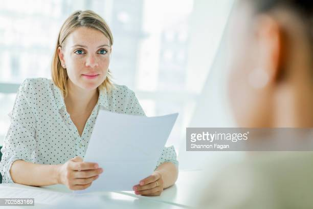 Woman reviewing resume report at conference table