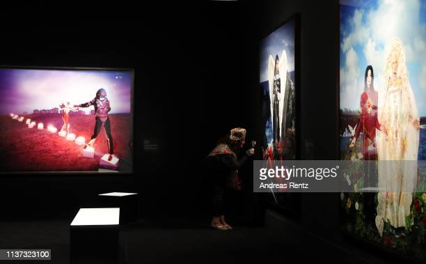 A woman reviews large format prints by David LaChapelle titled 'American Jesus' during the preview of the exhibition 'Michael Jackson On the Wall' at...