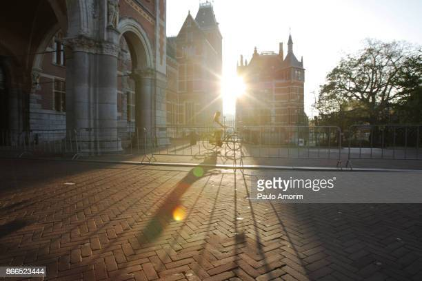 a woman ride bicycle in the moring in amsterdam - rijksmuseum stock photos and pictures