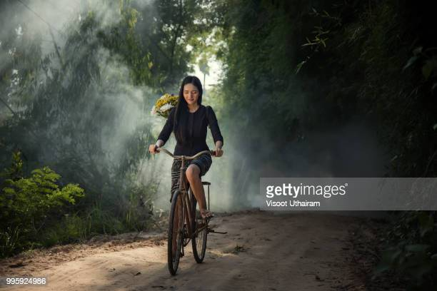 Woman ride on a bicycle along the road