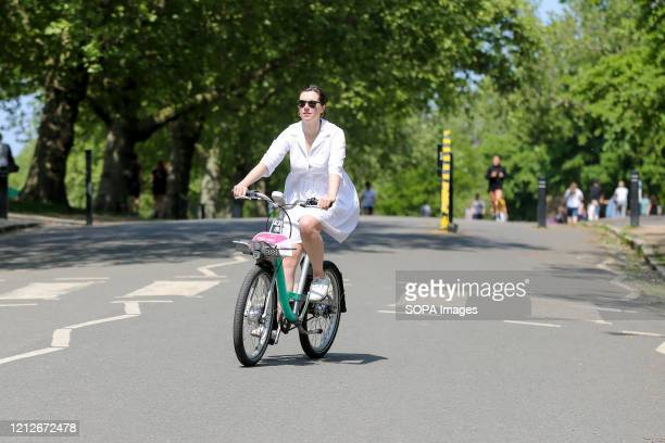 Woman rides a bicycle along the north London park on a warm and sunny day. Transport Secretary Grant Shapps has announced a £2 billion package to...