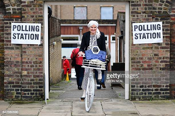 A woman rides a bicycle as she leaves a polling station at the Royal Hospital in Chelsea west London on June 23 as Britain holds a referendum to vote...