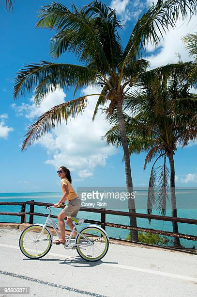 a woman rides a bicycle in florida. - key west stock photos and pictures