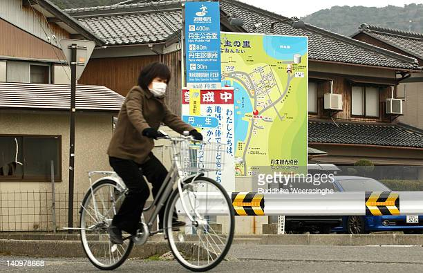 A woman rides a bicycle in front of an evacuation sign in the Mihama nuclear power plant evacuation zone on March 8 2012 in Mihama JapanOnly two of...