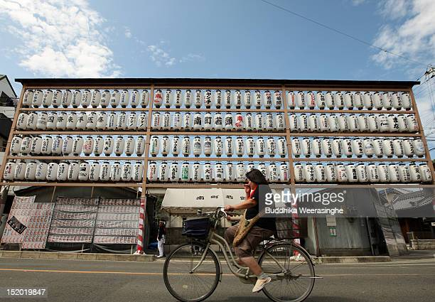 A woman rides a bicycle in front of roadside decoration lanterns during the Kishiwada Danjiri Festival on September 15 2012 in Kishiwada Japan The...
