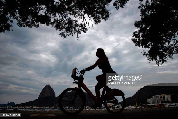 A woman rides a bicycle in front of the Sugar Loaf Mountain at Botafogo the neighbourhood south of Rio de Janeiro Brazil on March 17 2020 Rio de...