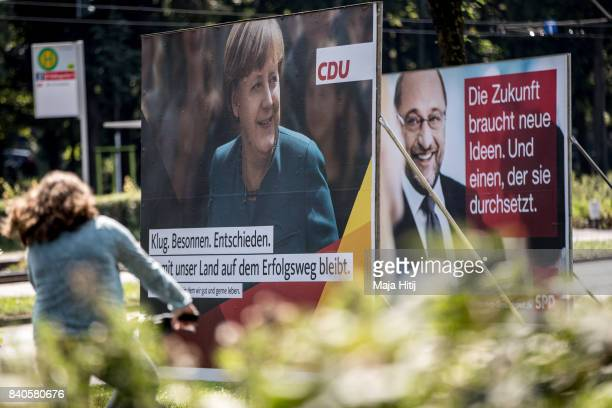 A woman rides a bicycle past election campaign billboards of CDU and SPD on August 29 2017 in Dusseldorf Germany Germany will hold federal elections...