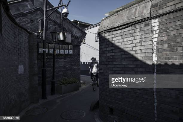 A woman rides a bicycle through an alleyway in a traditional hutong neighborhood in Beijing China on Sunday May 14 2017 Chinas economy is staging a...