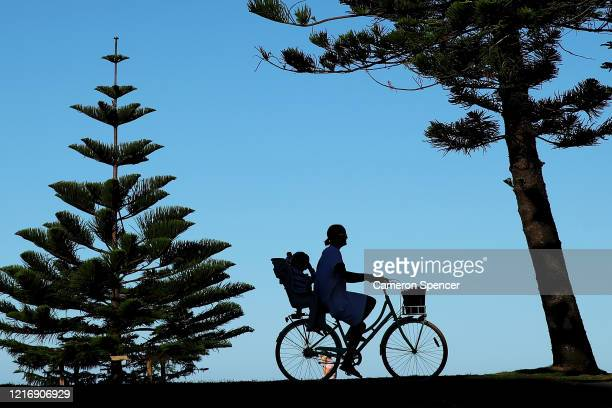 A woman rides a bicycle with her child at Manly Beach on April 05 2020 in Sydney Australia Northern Beaches Council today closed Manly North Steyne...