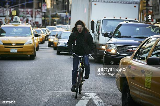 A woman rides a bicycle with traffic heading south through Times Square on March 23 2006 in New York City According to the Environmental Protection...