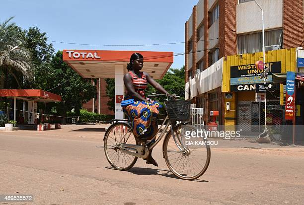 A woman rides a bicycles past a closed Total gas station in Ouagadougou on September 22 2015 Burkina Faso's coup leader Gilbert Diendere said on...