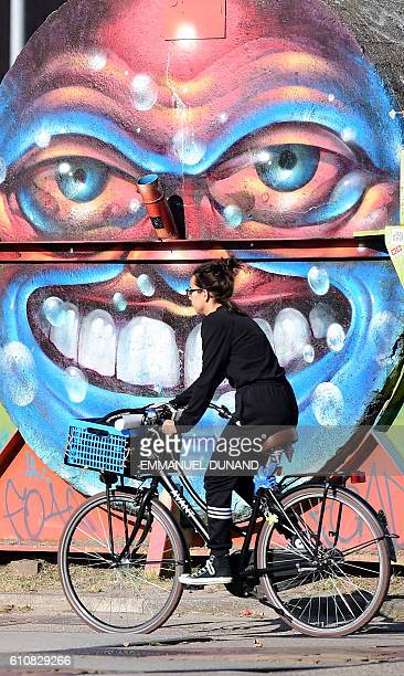 A woman rides a bike in front of street artist's works at at the NDSM shipyards in Amsterdam on September 27 2016 / AFP / EMMANUEL DUNAND /...