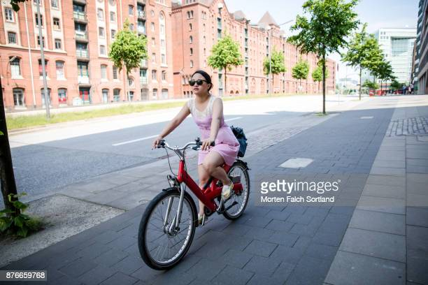 A Woman Rides a Bike through the Streets of Hafen City on a Spring Afternoon