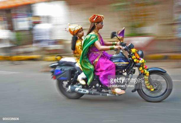 Woman rides a bike with her son during the Gudi Padwa celebrations at Girgaon on March 18, 2018 in Mumbai, India.