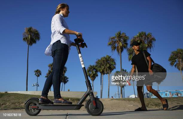 A woman rides a Bird shared dockless electric scooter along Venice Beach on August 13 2018 in Los Angeles California Shared escooter startups Bird...