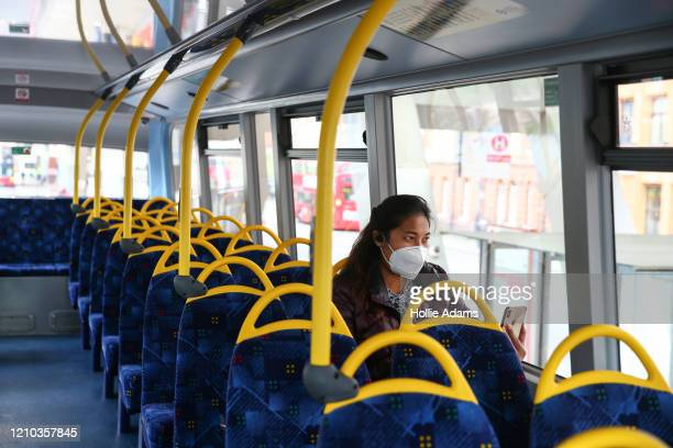 Woman rides a bus wearing a face mask on April 18, 2020 in London, England. In a press conference on Thursday, First Secretary of State Dominic Raab...
