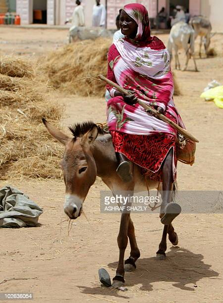 A woman rides a donkey in ElFasher the capital of North Darfur on July 5 2010 AFP PHOTO/ASHRAF SHAZLY