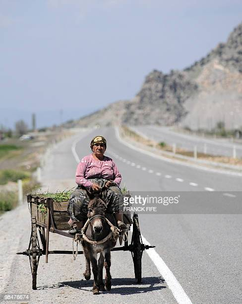 A woman rides a donkey on the side of the road during the 5th stage of the 2010 Tour of Turkey cycling race run between Denizli and Fethiye on April...