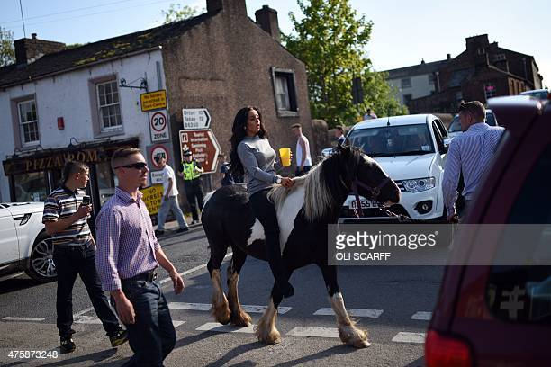 A woman rides a horse along The Sands road on the opening day of the annual Appleby Horse Fair in the town of ApplebyinWestmorland North West England...