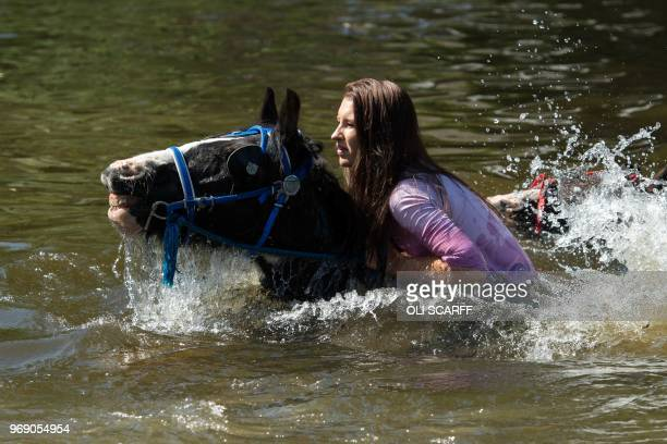 A woman rides a horse in the River Eden after washing it on the opening day of the annual Appleby Horse Fair in the town of ApplebyinWestmorland...