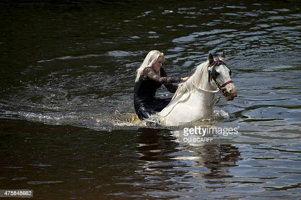 A woman rides a horse into the River Eden to wash it on the opening day of the annual Appleby Horse Fair in the town of ApplebyinWestmorland North...