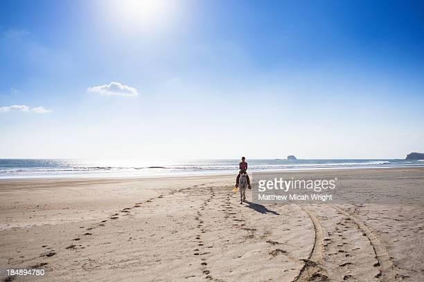 A woman rides a hose along the beach.