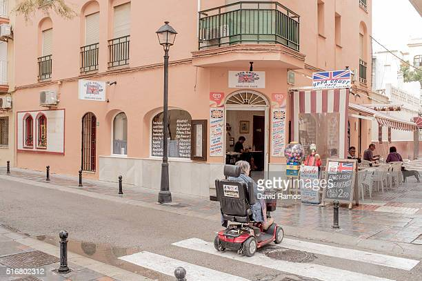 A woman rides a mobility scooter past an English bar on March 19 2016 in Fuengirola Spain Spain is Europe's top destination for British expats with...