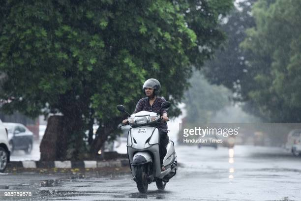A woman rides a scooter during the premonsoon showers near Sheikh Sarai on June 27 2018 in New Delhi India The monsoon rains are expected to arrive...