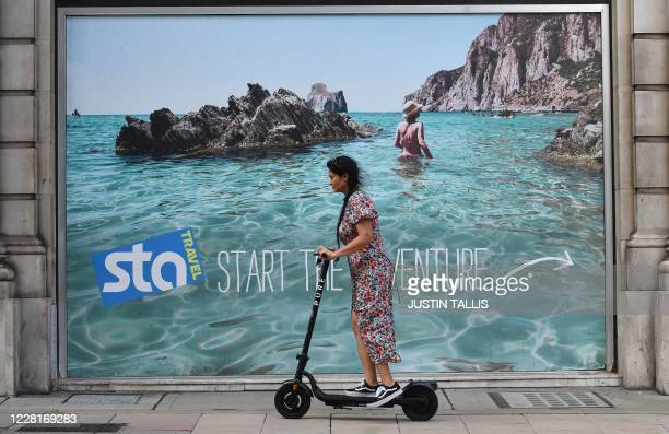 Woman rides a scooter past an advertising board outside a closed down branch of STA Travel near Victoria Station in central London on August 23,...
