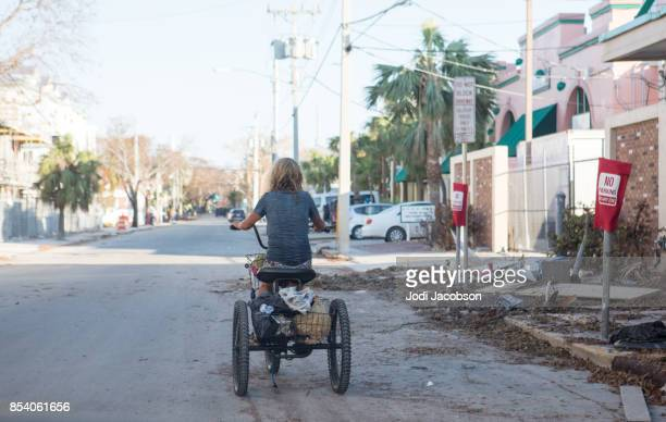 woman rides a tricycle down a deserted street in key west after a hurricane - jodi west stock photos and pictures